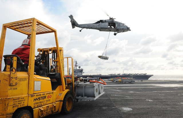 A helicopter lifts off the deck of USS George H.W. Bush.