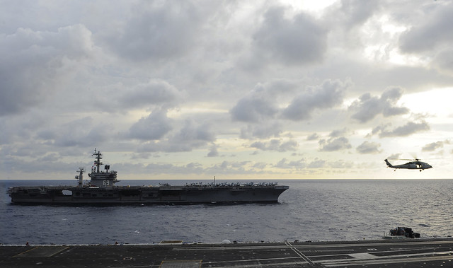 A helicopter approaches the flight deck of USS George H.W. Bush.