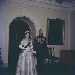 Queen Elizabeth wearing gown, sash and crown with Prince Philip in doorway / La Reine Élizabeth portant la toge, la ceinture et la couronne avec le prince Philipe dans une entrée de porte