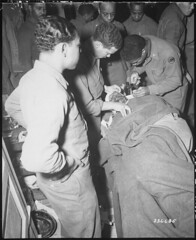 Capt. Ezekia Smith, 370th Inf. Regt., 92nd Div., receives treatment at the 317th Collecting Station, for shell fragments in face and shoulders suffered near Querceta, Italy. February 10, 1945. [24453000] #HistoryPorn #history #retro http://ift.tt/1VQwH1G (Histolines) Tags: italy history face station for near 10 shell smith retro timeline shoulders february 1945 capt collecting inf div treatment fragments 92nd receives vinatage regt suffered querceta 317th historyporn ezekia 370th histolines 24453000 httpifttt1vqwh1g