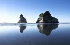 Wharariki Beach Reflections (Tim Bow Photography) Tags: world ocean travel blue light sunset newzealand mountain storm color colour reflection beach nature water rock easter landscape landscapes perfect exposure day alone quiet nelson symmetry clear reflect nz british welsh mass tasmansea washedup breathtaking isolated svenska goldenbay landscapephotography likeamirror whararikibeach timboss81 timbowphotography whararikibeachreflections