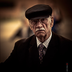 The Gentleman (Jeff Krol) Tags: street city portrait face hat canon square eos glasses eyecontact warm dof bokeh candid stripes suit explore f2 mustache wrinkles gentleman 1x1 2012 135mm 135l explored decently ecent 60d canon60d ef135mmf2lusm jeffkrol 20120519141147