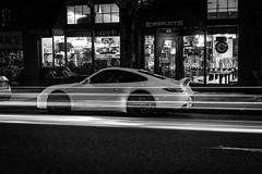 Porsche With Stripe (pillarsoflight) Tags: windows blackandwhite bw white black monochrome beauty night oregon 35mm dark portland prime grey restaurant store aperture nikon adobe porsche lane pdx desaturated headlight lighttrails 18 pnw lightroom twoway d3300