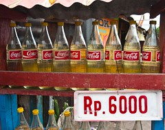 Petrol for sale, I wonder if the Coca Cola corporation approves of this unique re-cycling (turkishraf) Tags: indonesia petrol manado cokebottles pirogues microlet blackmarketpetrol manadolighthouse