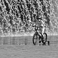 "Children on a bicycle (pedrosimoes7) Tags: street bw portugal water bicycle children blackwhite lisbon candid snapshot parquedasnações flickrduel blackandwhiteonly ""nikonflickraward"" streetpassionaward"