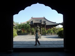 Temple Stroll (Chris Kealy) Tags: china door blue trees light sky woman tree silhouette by architecture dark way walking asian temple person bush asia arch bright stroller walk framed buddhist traditional chinese culture buddhism doorway walker frame passing archway framing shan shanxi bushes stroll passerby datong xi strolling