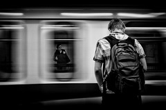 Other side of the world (. Jianwei .) Tags: street longexposure boy urban white motion black blur girl monochrome vancouver train wow 50mm mood pair sony platform transit backpack skytrain facetoface stillness newwestminster timing a55 columbiastation kemily tgam:photodesk=people2012 2012worldopenofphotography
