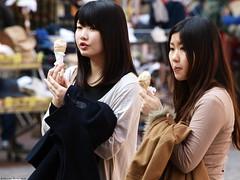 Girls and Ice-cream (ManOn Moon) Tags: street city girls portrait urban cute japanese spring europe dof cone candid olympus lick strasbourg eat enjoy icecream e3 rue 50200mm printemps share pleasure ville swd asiatic
