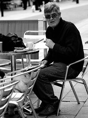 street portrait people urban bw food dog white man black male eye sunglasses pen glasses blackwhite shoes sitting eating candid seat streetphotography olympus shades drinks f18 staring greatyarmouth spectacles 45mm ep3 flickraward