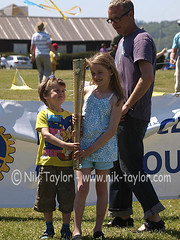 Children being photographed with an Olympic Torch, part of a charity fund raiser by the Exmouth and District Rotary Club kite festival, 26th &27th May 2012, The tourch is on loan from Colin Rowland who ran with the Olympic Torch last Monday in Hatherleigh (ontourwithdaisy.co.uk) Tags: charity boy girl kids children kid holding child young souvenir torch runners olympic runner hold fund raising raiser torchbearers torchbearer