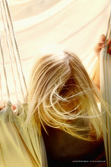 Young girl and beautiful blond hair movement in a hammock