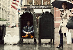 Finding Shelter (DayTripper15) Tags: nyc woman selfportrait mailbox umbrella manhattan flag shelter raining downpour facialexpression lafayettestreet ladyinthewindow candidstreetshot whatwefind usmailstoragebox sittinginamailbox ladyinthecafe queerinabox