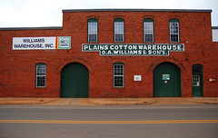 Warehouse (Samantha Evans of Samantha Evans Photography) Tags: street door wood windows light red sky brown sunlight white black reflection building brick green window glass sign yellow metal canon buildings reflections advertising grid wooden words doors pattern arch patterns bricks curves letters farming cement arches warehouse sidewalk brickwall americana powerline agriculture plains curve asphalt curb chemicals smalltown repeatingpatterns agribusiness repeatingpattern plainsga tamron1750 canon60d plainscottonwarehouse williamswarehouseinc oawilliamssons