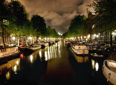 In Amsterdam the water is the mistress and the land the vassal. throughout the city there are as many canals and drawbridges as bracelets on a Gypsy's bronzed arms. (PhotoArt Images) Tags: amsterdam night boats canal image explore amsterdamatnight photoartimages
