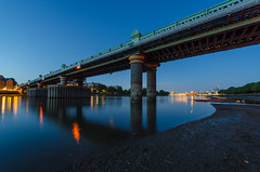 Fulham Railway Bridge at Low Tide (Torsten Reimer) Tags: uk longexposure bridge blue england london water thames night reflections river lights nacht unitedkingdom railway lowtide blau riverbank ufer fluss wandsworth themse putney reflektionen wandsworthbridge fulhamrailwaybridge