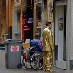 Goldmember #2 (Akbar Simonse) Tags: street people urban holland netherlands t candid wheelchair streetphotography denhaag thehague livingstatue goldmember frieten streetshot straat invalid kleinste vlaamse winkeltje straatfotografie straatfoto straatfotograaf akbarsimonse