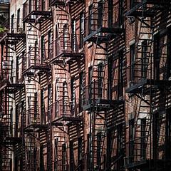 Fire Escape (mckenziemedia) Tags: newyork newyorkcity city urban building fireescape fireescapes ladders windows brick red black light illumination shadows