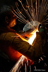 Life is dispersion of sparks (Captain Claw) Tags: portrait people yellow lowlight welding lifestyle sparkle grinding workingpeople dangerousjob weldingshop engineeringworkshop riskyjobs peopleworkingwithsparkle bangladeshiworkingpeople grindering
