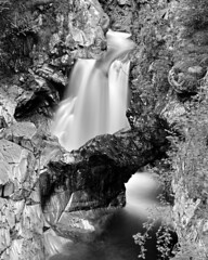 Falls of Bruar: Natural Arch (ShinyPhotoScotland) Tags: camera light blackandwhite art nature water monochrome beautiful composition manipulated river lens landscape photography scotland raw dynamic emotion unitedkingdom perthshire dramatic places equipment filter zen rivers balance flowing geology areas striking toned contrasts rugged turbulence elegance shapely gbr circularpolariser naturalarch rockstone digikam rockwater tonemapped nd4 olympuspenf bruar shapeandform dulllight rawconversion fallsofbruar intimatelandscape rawtherapee psammite naturehappens bruarwater luminancehdr olympus1260mmf28 motionstationary timefulness