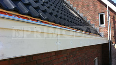 Dakdekker: Vooraanzicht van de houten betimmering waar de dakgoot in is gemonteerd door dakdekkers Rudy en Ridvan. Deze titaan zinken dakgoot is aan de voorzijde uitgevoerd met een kraal, montage in IJsselstein