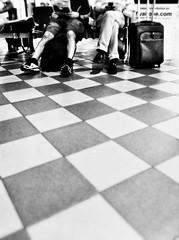 Ways of waiting (ale2000) Tags: camera people black men blackwhite airport floor legs squares pavement candid aeroporto luggage photowalk traveling bianco nero viaggio gambe uomini quadrati iphoneography snapseed