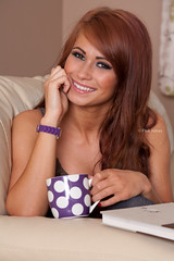 Beautiful woman at home sitting on sofa relaxing with drink (Phil Jones - That's Nice Photography) Tags: red portrait people woman brown white home cup coffee girl beautiful beauty face smiling female laughing hair relax happy person one office holding warm pretty day sitting colours purple adult tea drink head room watch young cream ivory lifestyle content location indoors health mocha age attractive kelly subject years concept brunette comfort relaxation foodanddrink gender caucasian 2025 weatherclimateandseasons