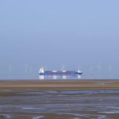 Millpond Reflections (JodBart) Tags: beach water still reflections horizon crosby blue sand orange turbines ship