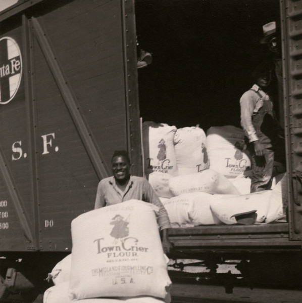 Worker transporting sacks of flour