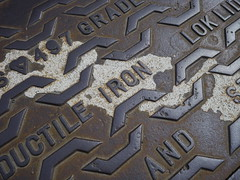 Ductile Iron Lok Lid (the justified sinner) Tags: street iron paint pavement glasgow panasonic cast cover manhole sewer f25 lid lok ductile 14mm gh2 justifiedsinner