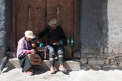 Quick Snack (vividcorvid) Tags: poverty china door people food woman abstract man architecture women asia exterior poor places tibet doorway eat gyantse pelkorchodemonastery