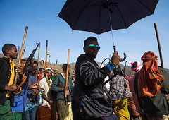 Oromo groom with an umbrella during his wedding celebration, Oromo, Sambate, Ethiopia (Eric Lafforgue) Tags: africa wedding people color men sunglasses horizontal umbrella religious outdoors groom togetherness gun day african muslim islam joy culture marriage happiness suit celebrations weapon guest ethiopia cheerful adults groupofpeople onthemove celebrating rayban islamic weddingceremony developingcountry indigenous ethnicity traditionalculture hornofafrica happily eastafrica kalashnikov abyssinia worldculture realpeople onlymen oromo lowangleview cheerfully traditionalceremony lifeevent modernityandtradition sambate ethio161194