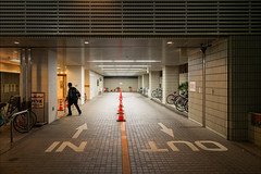 nagoya-1818-ps-w (pw-pix) Tags: door windows plants signs man lines japan night dark out walking lights moving parking bikes bicycles driveway tiles nagoya paving exit aichi shrubs entry cones paved pavers tiled witcheshats walkingbacktoouraccomodation nearfushimistation