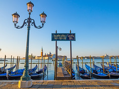 Gondolas (Nigel Wallace1) Tags: lighting venice red italy plants holiday church water buildings hotel boat jetty olympus tourists explore gondola lamps