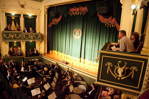 people watching orchestra from balcony seat
