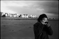 girl taking pictures on beach (gorbot.) Tags: winter sea blackandwhite bw beach rangefinder 35mmfilm f2 ayr roberta leicam6 kodaktrix400 mmount konicamhexanon50mmf2
