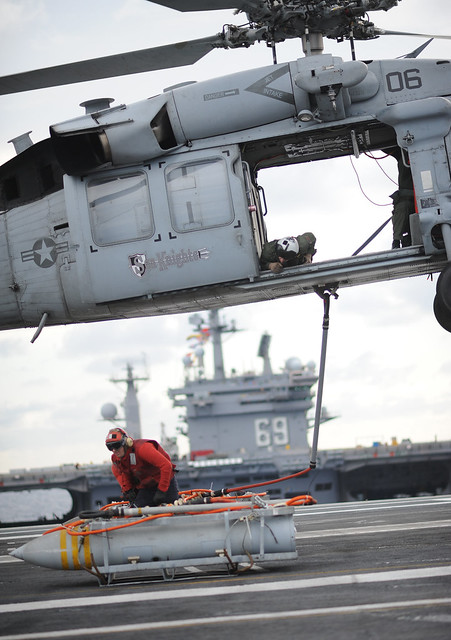 A helicopter lifts off the deck of USS George H.W. Bush. during a vertical replenishment.