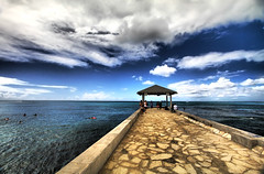Blue Sky in Waikiki (` Toshio ') Tags: ocean blue sunset sea people sun storm motion beach clouds person hawaii pier sand paradise waves pacific cloudy waikiki oahu jetty sandy perspective wave shore honolulu waikikibeach hdr highdynamicrange toshio