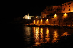 Vieste by night (SS) Tags: camera new light sea vacation italy white water colors june yellow night composition contrast buildings reflections photography gold wake waves glow angle wind pentax pov perspective scenic favorites framing nero tone comments vieste k5 lampione riflesso costaadriatica shimmers sooc