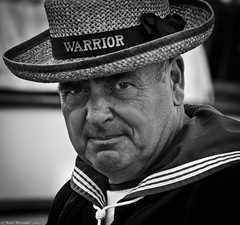 Welcome to Warrior. (Neil. Moralee) Tags: old uk sea bw white man black eye history face hat boat surf ship glare tide navy royal wave devon mature shore stare portsmouth sail warrior contact sailor portraite hms dockyard neilmoralee
