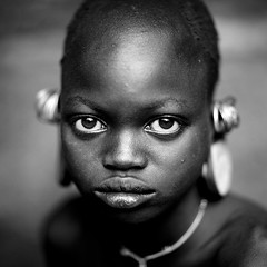Suri girl in Kibish, Omo valley, Ethiopia (Eric Lafforgue) Tags: africa portrait pierced people blackandwhite girl childhood square outside outdoors photography sadness bigeyes kid eyes day child sad serious bald earring culture tribal innocence omovalley tradition ethiopia tribe shavedhead ethnic surma hornofafrica ethnology omo eastafrica suri onepersononly realpeople lookingatcamera waistup 6583 africanethnicity pastoralist kibish snnpr onechildonly southernnationsnationalitiesandpeoplesregion kibbish ethiopianethnicity onekidonly onelittlegirlonly enlargedearlobe