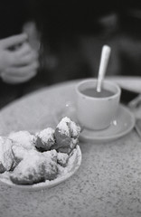 Beignet and Coffee (justinbrenneman) Tags: new bw white black film coffee monochrome table relax cafe orleans beignet grain du hp5 monde ilford