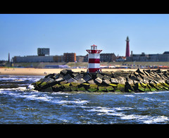 Small and tall (W.P.K) Tags: blue light red sea sky lighthouse holland netherlands dutch yellow photography pier photo sand waves harbour scheveningen stock nederland hague northsea beacon stockphoto stockphotography wpk wpk2
