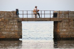 Fiddler on the pier Chania. (Betty Olsen) Tags: fiddler pier chania greece nature water sea evening sky man chair straw hat autumn