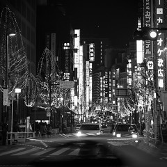Streets of Life (Marquisde) Tags: road street city light bw signs motion blur cars japan night canon buildings dark lights tokyo blackwhite movement shinjuku neon glow cityscape traffic nighttime 7d   canonefs1755f28isusm