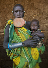 Mother and baby with lip plate, Kibish, Omo Valley, Ethiopia (Eric Lafforgue) Tags: africa portrait people color love vertical outside outdoors photography day mother bald culture tribal clay bracelet omovalley bangle tradition ethiopia tribe ethnic groupofpeople surma labret hornofafrica ethnology omo eastafrica suri 0803 realpeople  colorimage lookingatcamera waistup africanethnicity pastoralist lipplug lipplate stretchedlip kibish snnpr lipdisc southernnationsnationalitiesandpeoplesregion kibbish piercedhole piercedlipornament ethiopianethnicity enlargedearlobe bodymodification