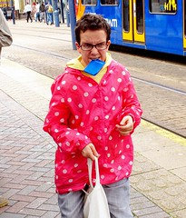 Sheffield (Don Jackson) Tags: road street pink red portrait people woman abstract colour bus strange mouth glasses weird women funny expression teeth profile pass photojournalism documentary surreal social polka dot grimace raincoat loud global