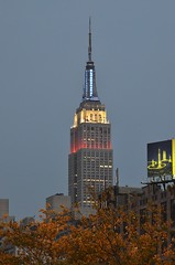 Empire State Building (Hoss Photon) Tags: new york city nyc newyorkcity blue trees red sky white building lights evening nikon empirestatebuilding nikkor d7000 24120mmf4gvr