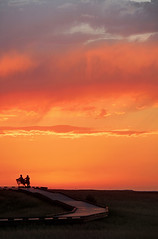 Enjoying a Badlands Sunset (Matt Champlin) Tags: travel sunset summer vacation sky people holiday storm weather southdakota canon bench landscape fun amazing colorful sitting peace hiking calming silhouettes tranquility husband stormy calm wife boardwalk badlands incredible badlandsnationalpark 2012 contemplation