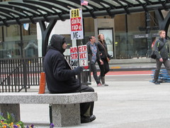 One man's war (Renee Rendler-Kaplan) Tags: city people signs man building male canon reflections bench him outside outdoors alone sitting protest may sit signage there he seated wbez chicagoillinois ignored chicagoist 2016 peoplewalking reneerendlerkaplan onemanswar canonpowershotsx530hs