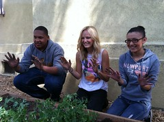 Malin Akerman & students show off their dirty hands from working in the garden